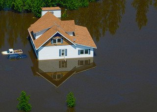 Water engulfs a home in a neighborhood in Minot, N.D., June 23. As many as 10,000 residents, about one-fourth of the city's population, have evacuated as the fast-rising Souris River inundates thousands of homes and businesses. The deluge from the Souris River is expected to exceed that of the city's historical 1969 flood, making this the region's worst flooding in four decades.